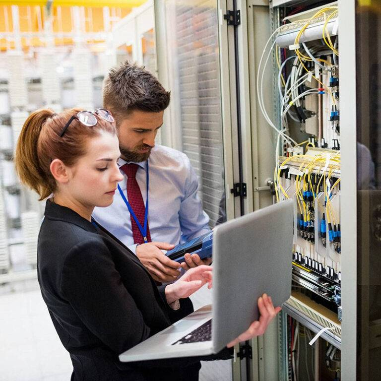 two-technicians-using-laptop-while-analyzing-server