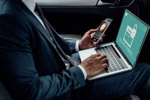 cropped view of african american businessman using laptop and smartphone in car with cyber security